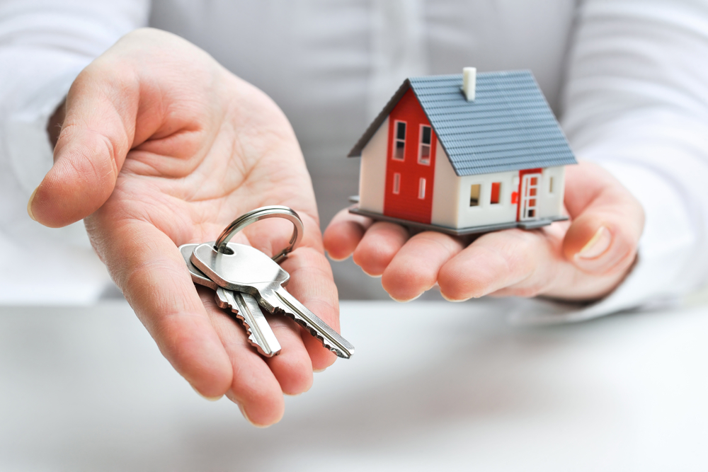 person-holding-house-and-keys